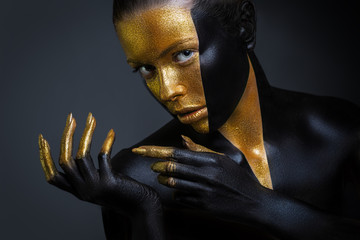 Beautiful girl with gold and black paint on her face and body. Female portrait with creative makeup.