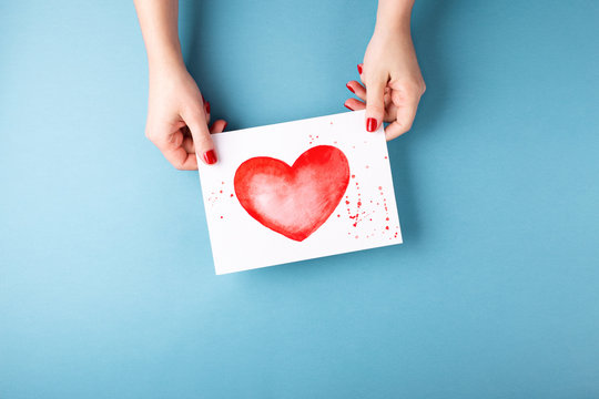 Female hands holding card with heart on blue background.