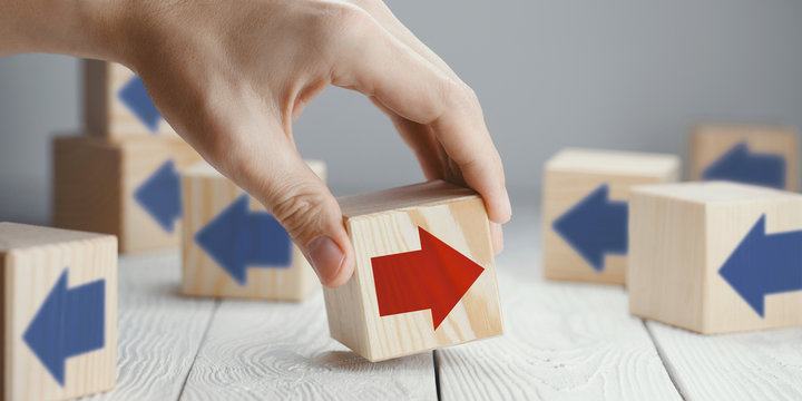 Hand putting a wooden cube with red arrow showing the opposite to blue arrows direction on neutral background