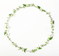 Round frame wreath made of spring wildflowers and leaves isolated on white background. Top view. Flat lay.