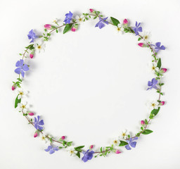 Round frame wreath made of spring wildflowers, lilac flowers, pink buds and leaves isolated on white background. Top view. Flat lay.