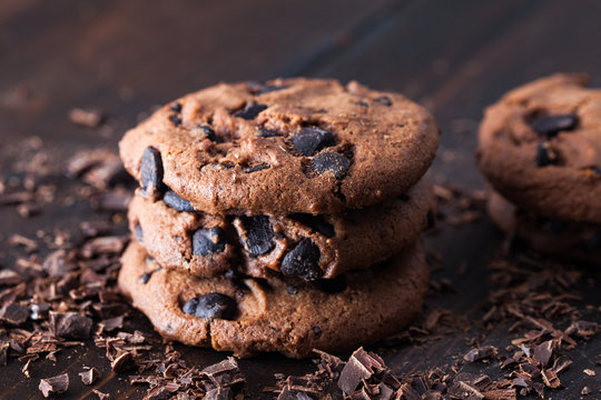 Homemade chocolate cookies on dark old wooden table. Chocolate chips cookies shot
