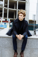 Portrait of a handsome, attractive, young man in a blue suit, coat, in the city. pensive and sad, waiting.