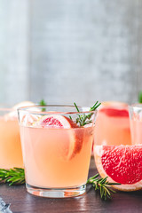 Fresh pink alcoholic cocktail with grapefruit, ice and rosemary