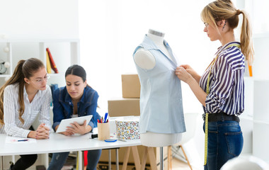 Group of fashion designers working and deciding details of new collection of clothes in the sewing workshop.