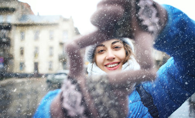 portrait of a young smiling attractive woman in warm winter clothes at sowy day on the street background. woman shows a frame from hands like photo. Photo Frame Hands Made By A Hipster young girl