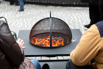 People warm themselves by the fireplace in the street.