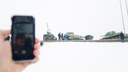 Mobile phone in hand on the background of old military equipment with reflection on the phone screen