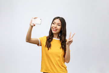 Image of excited happy young woman isolated over grey background make selfie by camera.