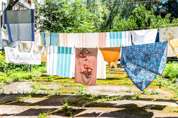 Many hanging clothes in summer garden with colorful shirts drying on rack in Ukraine or Russia by Soviet apartment buildings