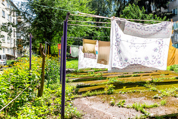 Many hanging clothes rows in summer garden with colorful shirts drying on rack in Ukraine or Russia by Soviet apartment buildings