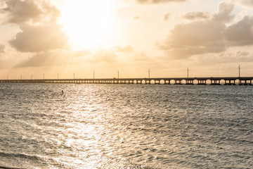 Seven Mile Bridge landscape of Florida Keys reflection of sun on water atlantic ocean and Overseas Highway road with horizon clouds sunset rays