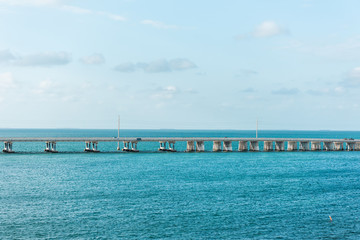 Seven Mile Bridge landscape of Florida Keys turquoise blue water atlantic ocean and cars on Overseas Highway road with horizon clouds