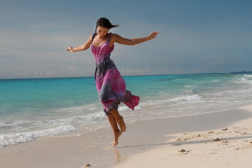 Happy brunette on tropical beach dancing on wet sand