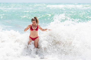 Young woman standing in red swimsuit bikini bathing suit scared surprised by splash crashing wave in Hollywood, Miami Beach Florida green water drops