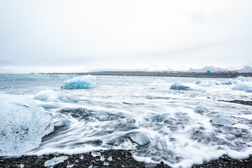 Landscape of blue glacier icebergs in Jokulsaron diamond beach in Iceland with black sand and long exposure of water waves