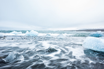 Landscape view of blue glacier icebergs in Jokulsaron lagoon lake diamond beach in Iceland with black sand and long exposure of water waves