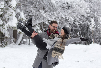 Man lifting girl in snow in forest