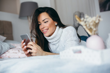 Woman using smartphone on the bed