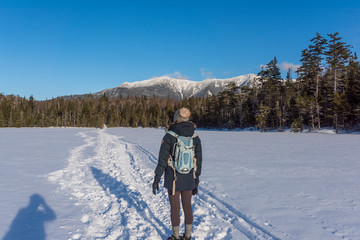 a photographer takes a picture of a woman standing on a frozen lake with the White Mountains int he background