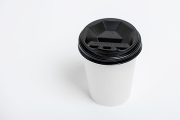 One focused take away white paper cup with black cap presented in front, isolated on simple gray background