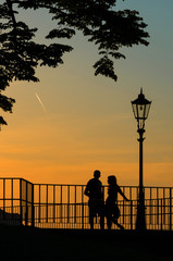 Silhouette of a couple in love at sunset next to the lamppost