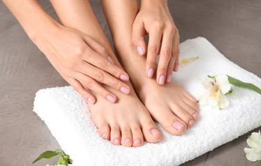 Woman touching her smooth feet, towel and flowers on grey background, closeup. Spa treatment