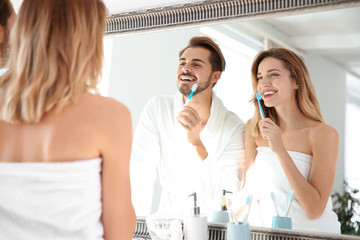 Young couple with toothbrushes near mirror in bathroom. Personal hygiene