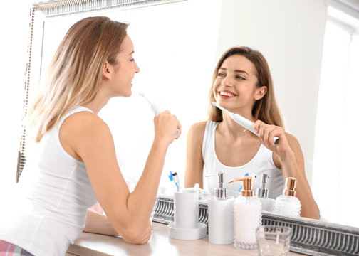 Young beautiful woman with toothbrush near mirror in bathroom. Personal hygiene
