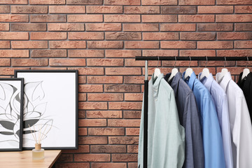 Wardrobe rack with stylish clothes near brick wall in dressing room
