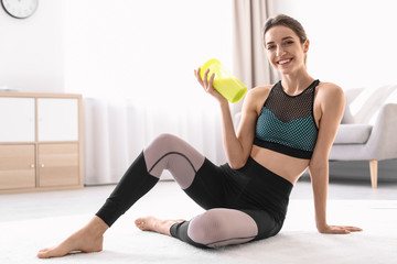 Young sporty woman with bottle of protein shake sitting on floor at home. Space for text