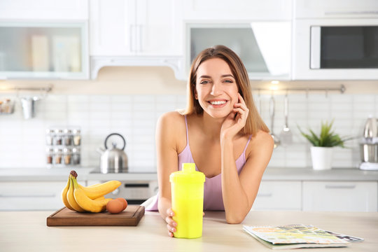 Young woman holding bottle of protein shake at table with ingredients in kitchen