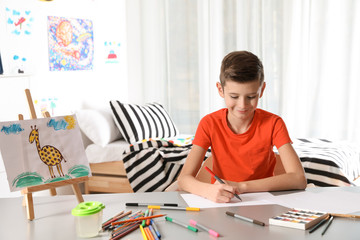 Little child drawing picture at table with painting tools indoors