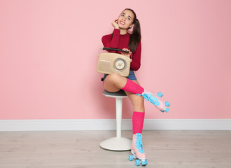 Young woman with roller skates and retro radio sitting on chair near color wall