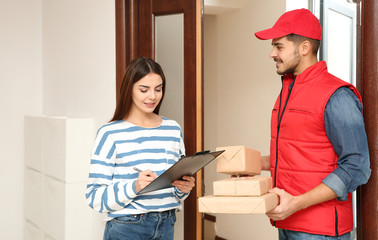 Woman receiving parcels from delivery service courier indoors