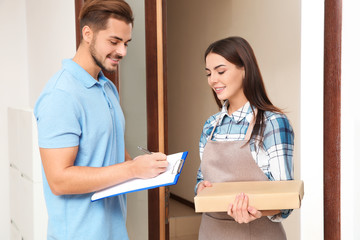 Client receiving parcels from delivery service courier indoors