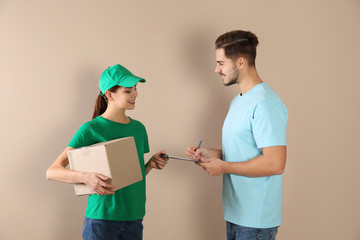Client receiving parcel from delivery service courier on color background