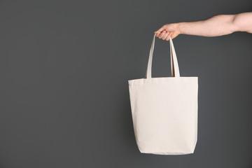 Man holding cotton shopping eco bag on grey background. Mockup for design