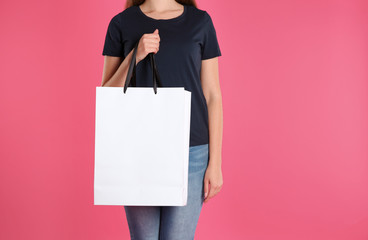 Woman with paper shopping bag on color background. Mock up for design