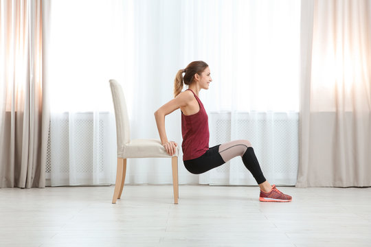 Young woman exercising with chair indoors. Home fitness