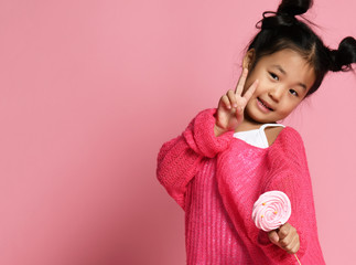 Happy young asian little girl kid lick eat happy big sweet lollypop candy on pink  Wall mural