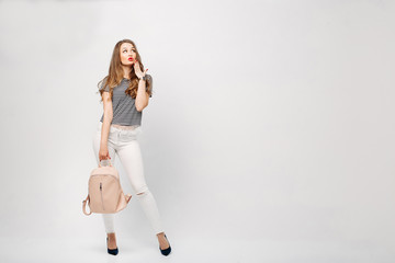Fashionable and stylish woman with long wavy hair,red lips making duck face, surprised looking up. Girl wearing in blouse, white jeans, with leather bag, dreaming and touching face by finger. Fashion