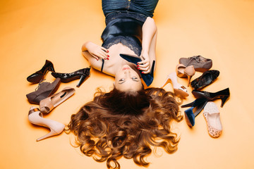 Beautiful girl  lying on yellow at studio among many fashionable shoes and imitating conversation like call phone. Brunette woman with long curly hair emotionally posing, holding heel in hand.
