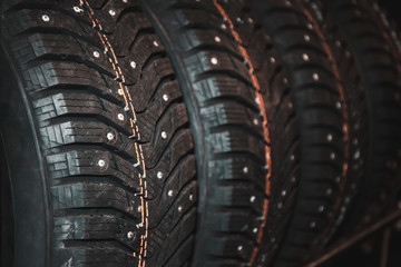New winter studded tyre with metal spikes in store, rubber auto car wheels