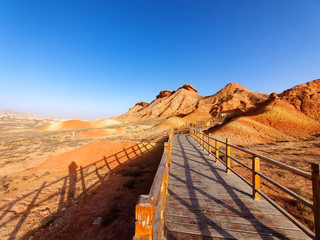 Aluminium Prints Brown Walking paths around sandstone rock formation at Zhangye National Geological Park. Zhangye Danxia National Geopark, Gansu, China. Colorful landscape of rainbow mountains with blue sky background.