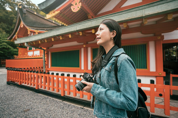 photographer standing near red wooden temple