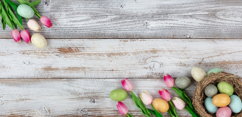 Springtime tulips and colorful eggs on rustic wooden boards for Easter holiday background