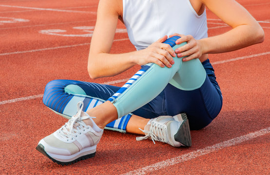 Sport knee injury. Woman has pain in knee after run outdoors