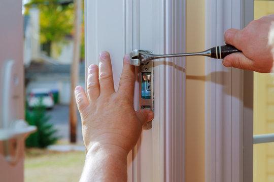 Closeup of a professional locksmith installing or repairing a new deadbolt lock