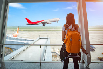 woman passenger of the airplane keep standing by in waiting hall for boarding the aircraft for arrival/departure, looking live incoming and outgoing airplane in the hall